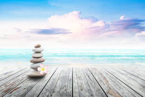 Pebble stones stacked up with a flower on the wooden platform facing the sea.