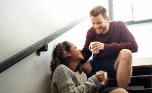 happy couple sharing a cup of coffee sitting on stair